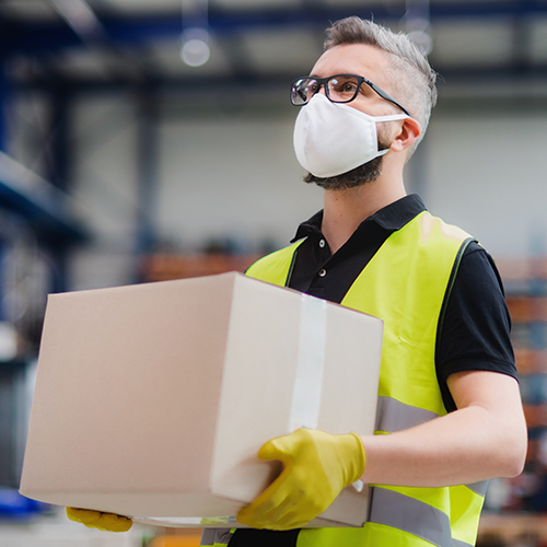 Man wearing mask, carrying box
